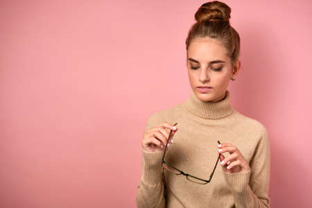A girl with a high beam stands in a sweater on a pink background and looks at the glasses in her hands.