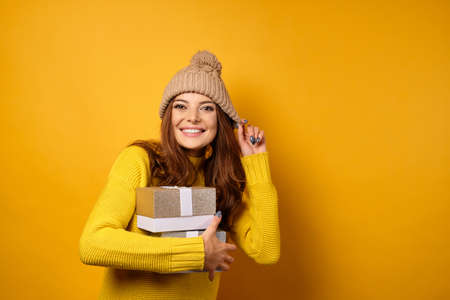 Beautiful brunette in a yellow sweater and stands on a yellow background with gift boxes and adjusting his hat.
