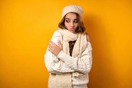 Portrait of a girl wrapped in a scarf in a white sweater and hat standing on a yellow background with a displeased face
