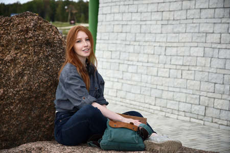 The red-haired girl in a blue shirt and jeans sits on a stone with a backpack in her hands and smiles.