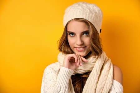 Portrait of a girl in a white scarf and hat standing on a yellow background and looking at the camera.