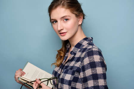 Close portrait of a girl with blue eyes in a plaid shirt on a blue background with a book and glasses in hands.