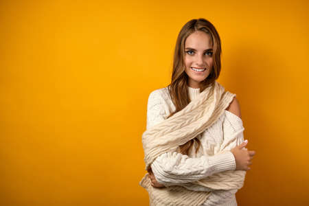 A beautiful girl is standing on a yellow background in a white sweater, wrapping in a scarf, hugging herself and smiling Zdjęcie Seryjne