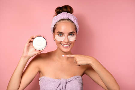 A beautiful girl with a bandage on head with patches under eyes stands on a pink background, points finger at the cream in hand Zdjęcie Seryjne
