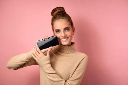 A girl in a turtleneck with a high beam on her head stands on a pink background smiling and holding the phone with a frame screen