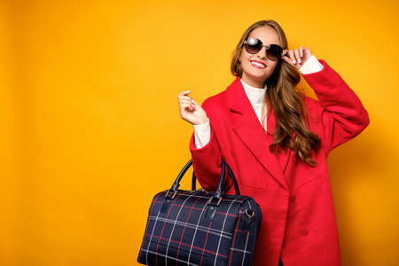 A beautiful girl with red lips is standing in a red coat on a yellow background with a travel bag and adjusting sunglasses.