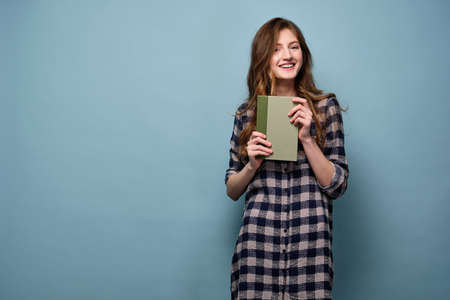 A blond-haired girl in a plaid shirt stands on a blue background, holding a book in front of him and laughing. Banco de Imagens