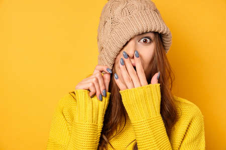A beautiful brunette in a yellow sweater pulling a hat over the half-sleeve, covering her mouth with her hand with assurance.