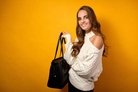 A beautiful girl in a white sweater smiling is standing on a yellow background and holding a big black bag in her hand.