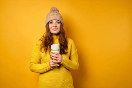 A beautiful brunette in a yellow sweater and hat stands on a yellow background and holds a white thermomug in her hands.