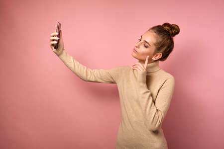 A girl with a high beam stands half a turn in a sweater on a pink background and takes a selfie. Zdjęcie Seryjne
