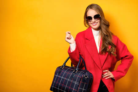 A girl with curls, red lipstick in a red coat and sunglasses stands on a yellow background with a travel bag and smiles.