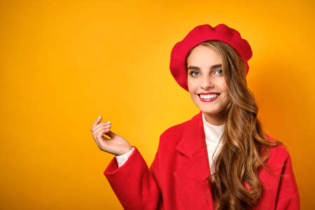 Girl with curls, red lipstick in a red coat and beret is standing on a yellow background, smiling. Stock Photo