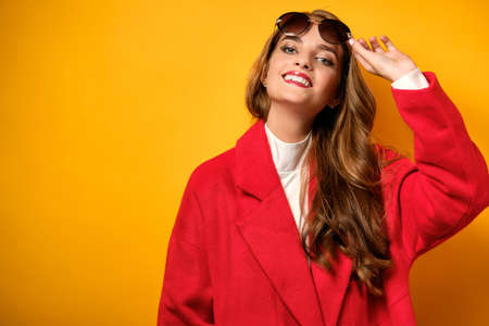A girl with curls, red lipstick in a red coat is standing on a yellow background and holding up sunglasses, smiling.