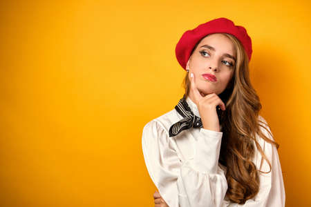 A beautiful blonde with red lips in a white blouse and a red beret looks thoughtfully at the side, pressing a finger to her face.