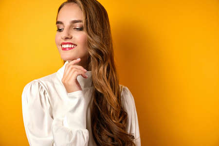 A girl with red lips and curls in a white blouse stands smiling and looks away on a yellow background.