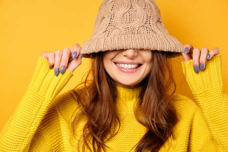 A brunette stands on a yellow background in a yellow sweater, pulling a hat over a half-shirt and smiles