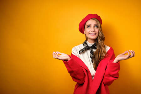 A beautiful blonde with red lips in a white blouse and a red beret looks up embarrassed, spreading her arms to the sides.