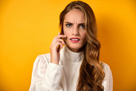 A beautiful girl with red lips stands on a yellow background, talking on the phone with a displeased frown.