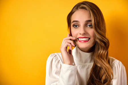 A girl with red lips and curls in a white blouse stands with a taut smile and speaks on the phone on a yellow background.