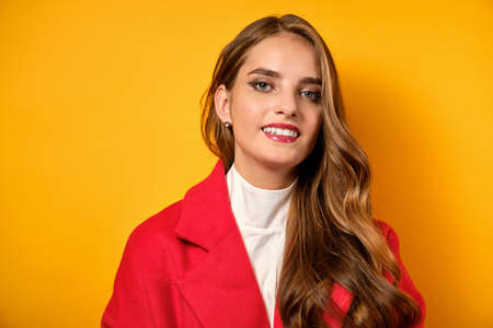 Beautiful girl with red lips stands in a red coat on a yellow background. Stock Photo