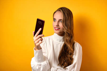 A girl with red lips and curls in a white blouse looks in surprise at a smartphone, standing on a yellow background. Stock Photo