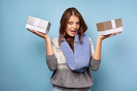 A brunette in a sweater and scarf stands on a blue background with gift boxes on her palms and looks into the frame.
