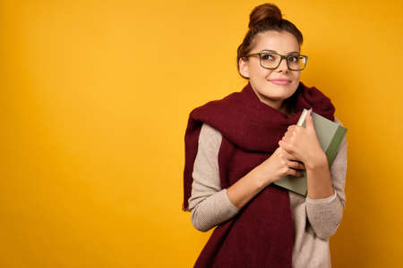 A brunette with glasses and a burgundy scarf, with a high bun clutching a book to herself and dreamily looks up.