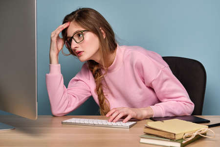 A girl with a braid in a pink sweater and glasses sits in front of a computer and looks tiredly at the monitor on the keyboard