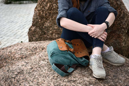 A close shot of the crossed legs of a girl sitting on a stone and a backpack nearby.