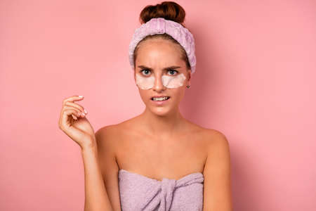 A girl with clean skin stands on a pink background in a towel and with patches under her eyes looks displeasedly at the camera.