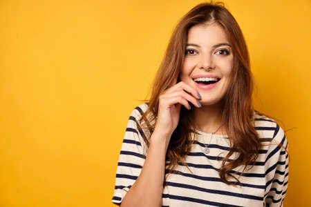 Cute brunette in a striped T-shirt laughs on a yellow background. Фото со стока