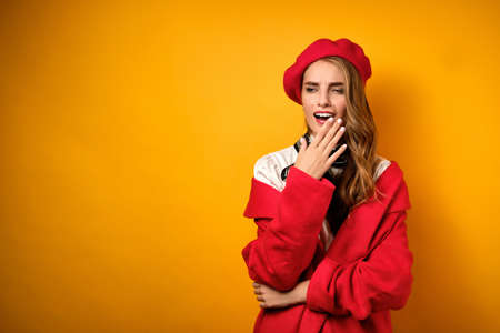 Portrait of a beautiful yawning blonde with red lipstick, in a white blouse, red coat and beret on a yellow background.