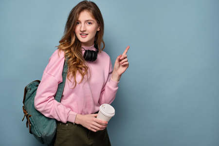 A girl with a backpack, headphones on her neck stands on a blue background with a paper cup and points her finger to the side. Фото со стока