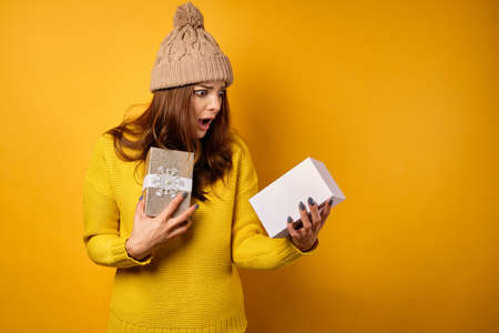 A brunette in a yellow sweater and hat stands on a yellow background and looks in shock at the open second-hand box