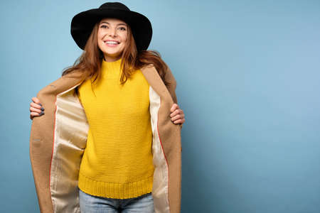 A brunette in a yellow sweater and black hat stands on a blue background, revealing a beige coat to the sides.