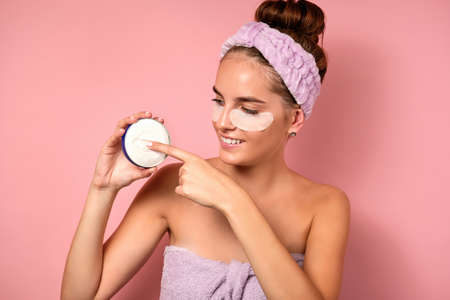 A girl with a bandage on her head and patches stands on a pink background, holding a jar of cream and runs a finger over it Фото со стока