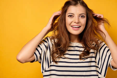 A brunette in a striped T-shirt stands on a yellow background, joyfully looks into the camera, throwing hair away from the face Фото со стока