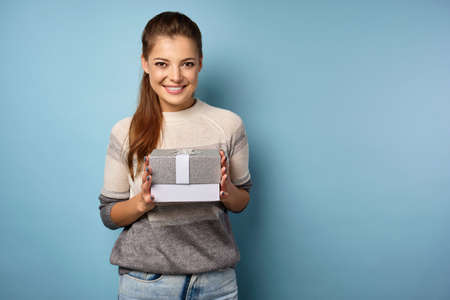 Joyful brunette holds a gift box in her hands and smiles. Фото со стока