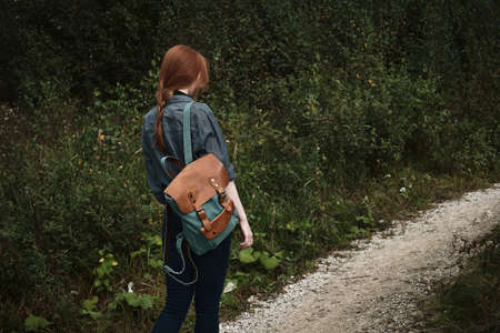 A redhead girl with a scythe in a denim shirt is walking along the road with a backpack, a frame from the back.