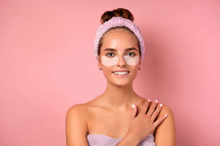 A girl with a bandage on her head and patches under her eyes stands on a pink background with her hand on her shoulder Фото со стока