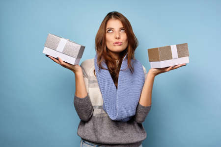 A brunette in a sweater is looking dreamily at the top, biting her lip and holding gift boxes in the palm. Фото со стока