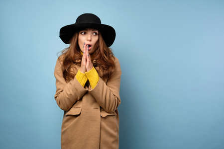 A brunette in a yellow sweater, hat and coat looks in astonishment to the side with her hands clasped in front of her.