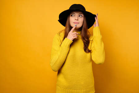 The brunette in a yellow sweater and black hat looks thoughtfully to the side with her finger to her lips. Фото со стока