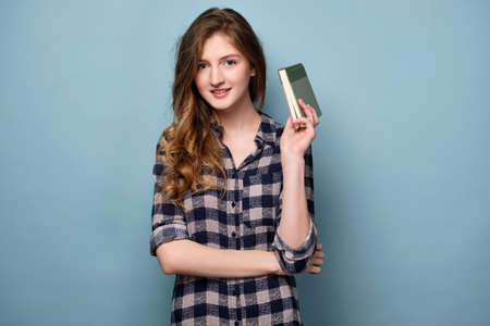 A girl in a plaid shirt stands on a blue background and smiles while holding a book in her hand