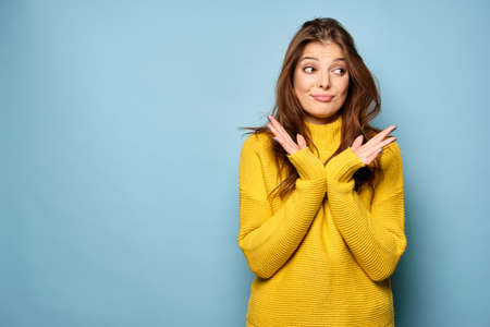 A brunette in a yellow sweater is standing against a blue background, and with incomprehensible pouting of her lips looks to the side.