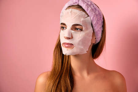 Portrait of a girl with a bandage on her head, a fabric mask on her face and bare shoulders on a pink background.