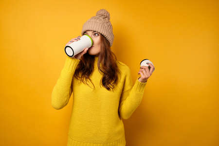 A brunette in a yellow sweater and hat stands on a yellow background and takes a sip from a white thermocup.