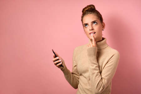 A girl with clean skin and a high bun is looking thoughtfully at the top with finger to lips and holding a smartphone in her hand