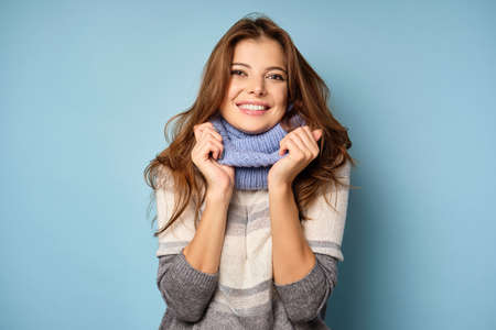 A beautiful brunette in a sweater and scarf stands on a blue background, smiling broadly at the frame.
